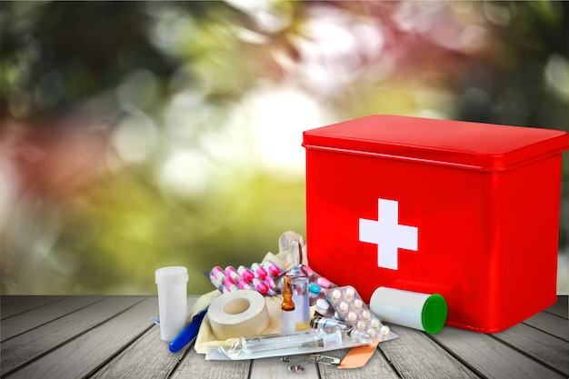 First aid kit with medical supplies on wooden background