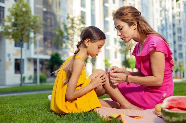 응급 처치. 그녀에게 응급 처치를 제공하면서 그녀의 딸 무릎에 석고를 씌우고 좋은 즐거운 여자