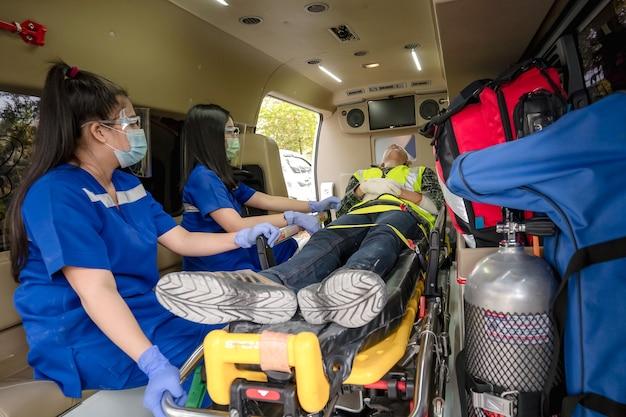 患者を転送するための応急処置トレーニング、感覚の喪失または正常な動きの喪失。救急隊員が救急車の担架に乗った男性を救急車に乗せます。