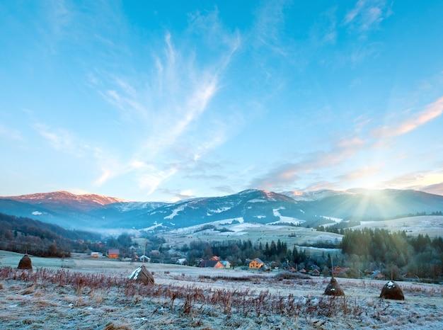 Первые осенние заморозки на пастбище со стогами сена и восход солнца в горной деревне