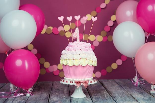 ボールと紙の花輪とピンクの背景にユニットを持つ最初のバースデーケーキ。