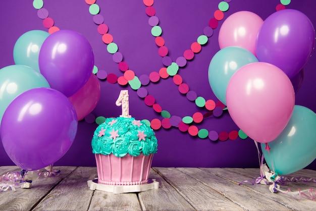 ボールと紙の花輪と紫色の背景にユニットを持つ最初のバースデーケーキ。