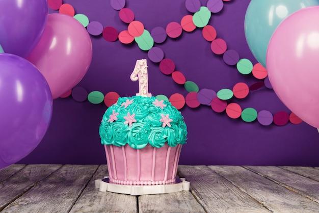 공 및 종이 갈 랜드와 보라색 배경에 단위와 첫 번째 생일 케이크.