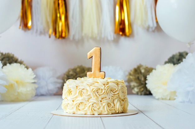 First birthday cake with number one on top. cake smash party. festive decor in beige and golden colors.