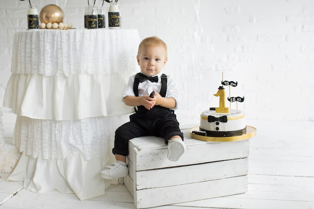 The first birthday of the child. one year with a cake. child in a tuxedo