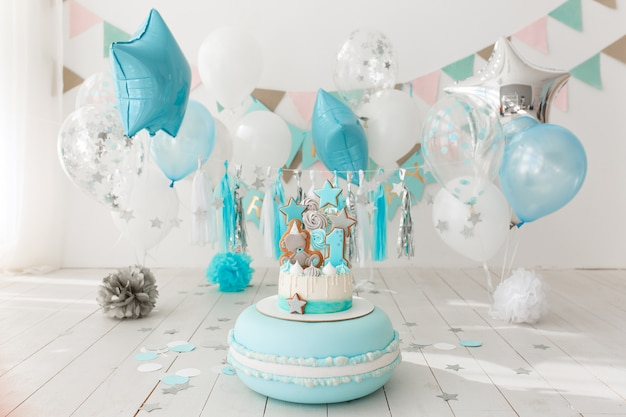 First birthday decorated room with blue cake standing on big macaroon