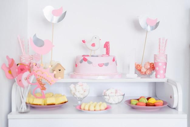 첫 번째 생일 파티 개념입니다. 달콤한 케이크와 섬세한 핑크 색상의 장식 품목이 들어간 캔디 바.