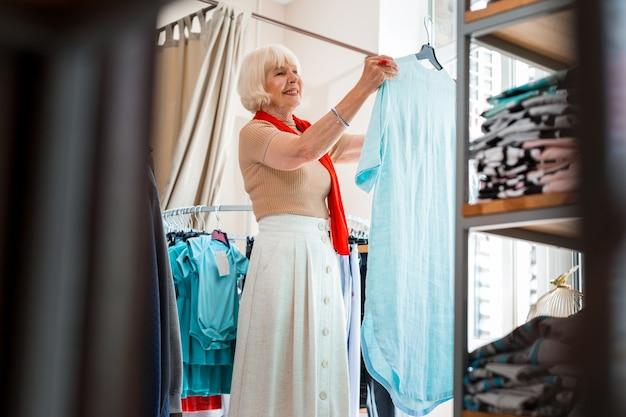 最初に選んだ。夏のドレスを手に持って衣料品店に立っている間、賞賛を表現する感情的な白髪の女性