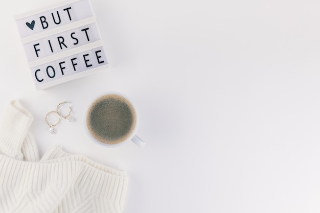 But first coffee text on lightbox with coffee cup and white background