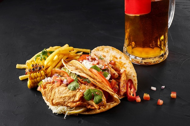 First corn tortilla with grilled chicken fillet second with fish fillet french fries sauce and beer ...