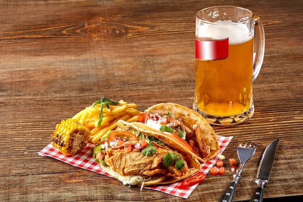First corn tortilla with grilled chicken fillet second with fish fillet sauce and beer on wooden table