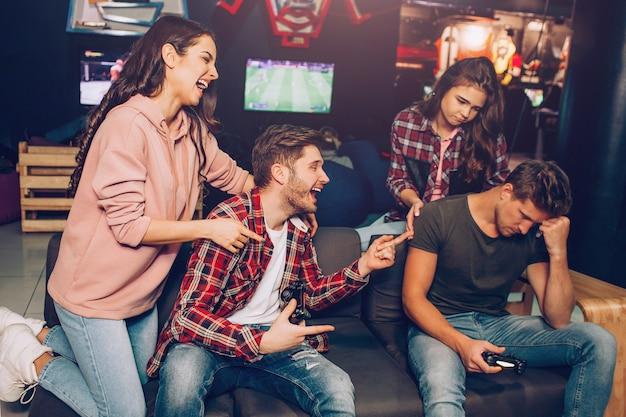 Первая пара смеется над второй. они выигрывают игру. люди сидят в комнате. ребята держат джойстики.