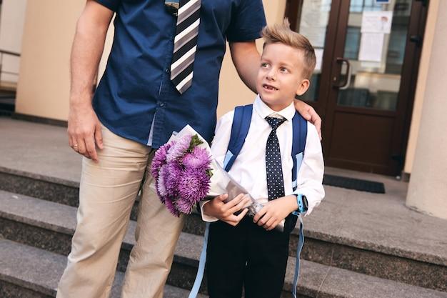 Первый день в начальной школе. отец держит сына за руку. ученик начальной школы в форме. начало уроков. обратно в школу. первый день осени.