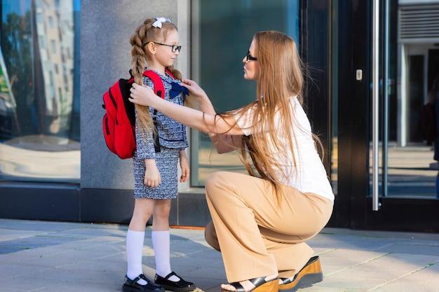 秋の初日。学校の子供たちに戻る。母親は一年生の小さな女子高生のランドセルをリードしています。