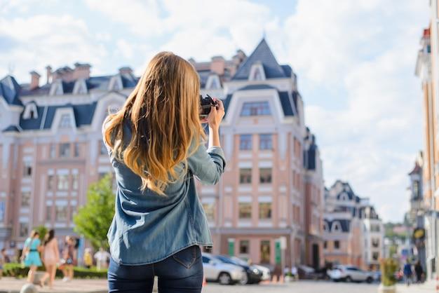 新しいヨーロッパの都市での初日。デジタルカメラで家の写真を撮る美しい女性。彼女はカジュアルな服を着ています。後ろから見る、ぼやけた背景