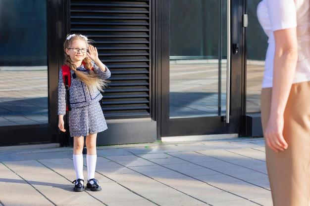 가을의 첫날. 다시 학교 아이들에게. 어머니는 제복을 입은 작은 여학생을 이끌고 1학년 때 책가방을 씁니다. 수업 시작. 아이가 엄마에게 손을 흔든다.