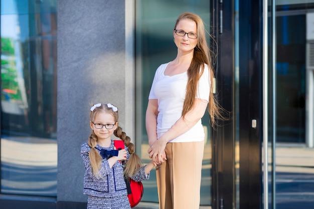 秋の初日。学校の子供たちに戻る。母親は1年生の女子高生をリードしています。