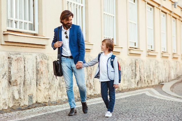 First day at school. dad leads a son in first grade. father with kid holding hands at street. back to school conept.