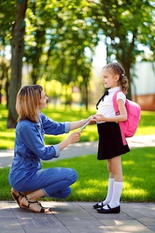 First day at school. mother leads a little child school girl in first grade. woman and girl with backpack behind the back. beginning of lessons. first day of fal