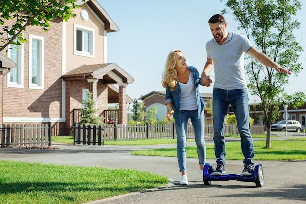 첫 경험. 처음으로 셀프 밸런싱 스쿠터를 타는 남편의 손을 잡고 즐거운 웃는 여자가 그를 지원합니다.