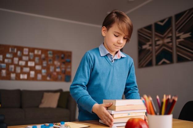 집에서 공부하고, 책을 들고, 온라인 수업을 준비하는 1 학년 소년