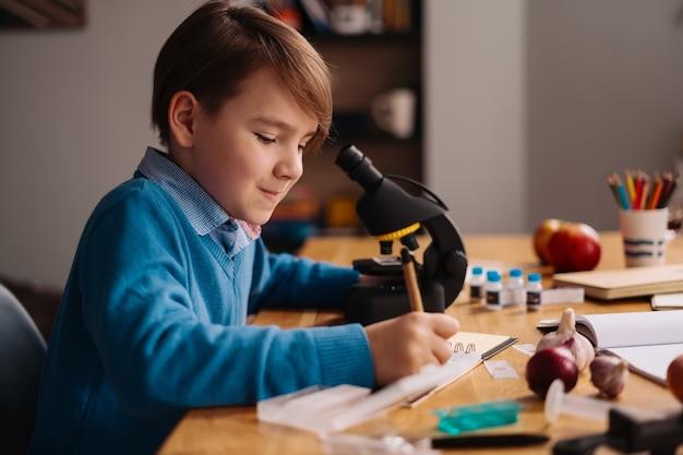 Первоклассник учится дома с помощью микроскопа