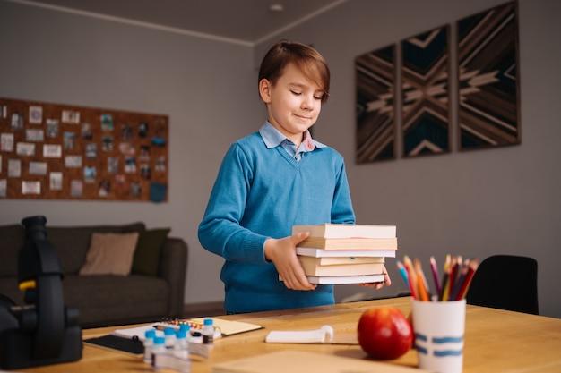 Ragazzo di prima elementare che studia a casa, con in mano un mucchio di libri, si prepara per la lezione online