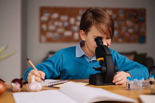 First grade boy studying at home using microscope