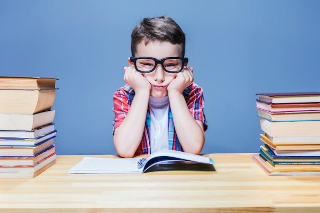 Первоклассник разучивает домашнее задание в школьной библиотеке. ученик в очках против многих книг