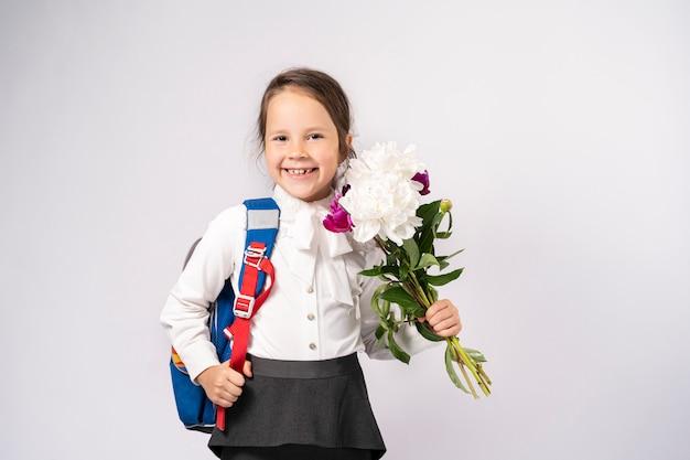 花とバックパックを保持している白いシャツの1年生の女の子