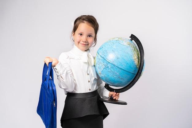 Первоклассник держит глобус в одной руке и сумку для тренировок в другой