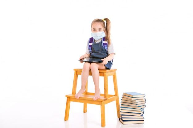 Первоклассник в медицинской маске учится читать. маленькая девочка на дому дистанционного обучения. ребенок в медицинской маске работает на ноутбуке и книги. уроки делаю.