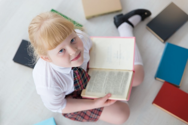First grader is sitting on the floor with books