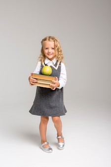 First-grader with books and an apple smiling on a bright background