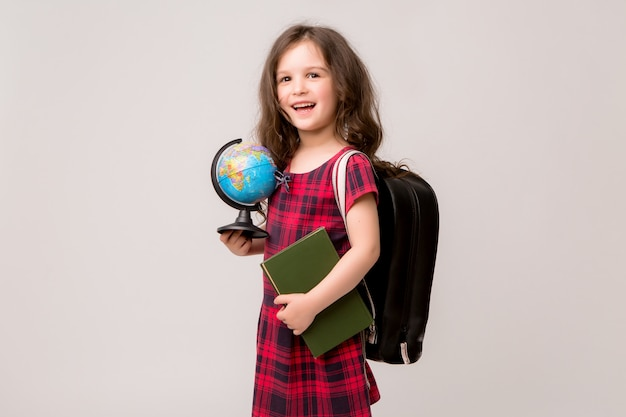 First-grader with books and a globe smiling