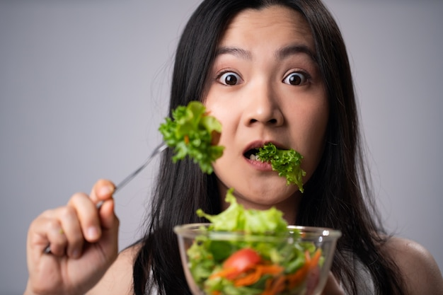 First impression asian woman eating salad isolated over white wall. healthy lifestyle with clean food concept.