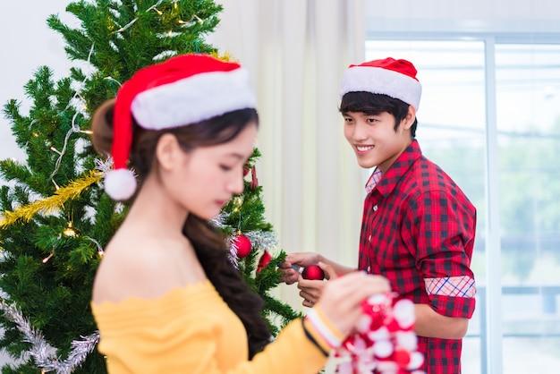 クリスマスツリーを飾る準備をしている男性と女性の第一印象