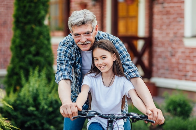 First lessons bicycle riding. handsome grandather teach his granddaughter to ride a bike.