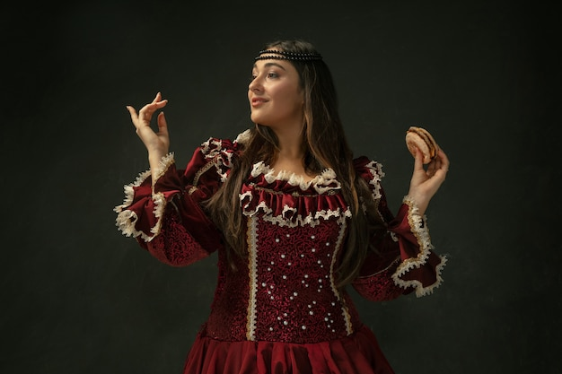 First love. portrait of medieval young woman in red vintage clothing holding burger on dark background. female model as a duchess, royal person. concept of comparison of eras, modern, fashion, beauty.