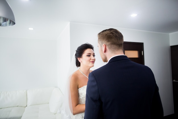 The first meeting. the groom comes into the room to the bride with a bouquet.