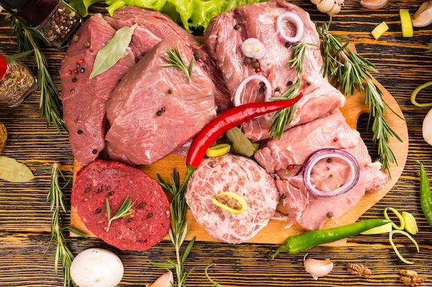 나뭇결 테이블에 둘러싸인 조미료와 함께 원시 쇠고기와 돼지 고기의 1 인칭 시점과 풍부한