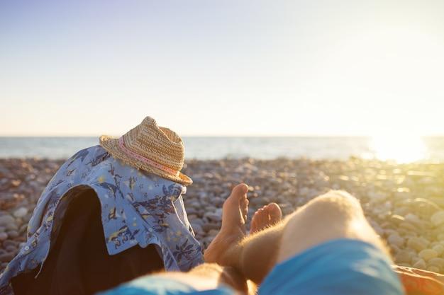 サンセット ビーチでの男の足の一人称視点。旅行のコンセプト