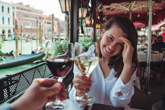 Точка зрения первого лица пара в кафе на открытом воздухе пьет вино улыбается женщина гранд канал венеции
