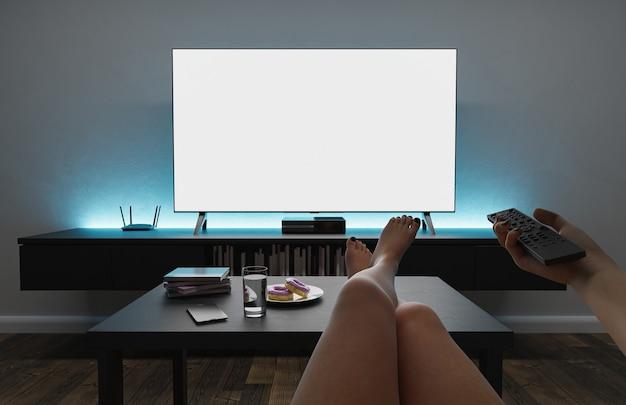 Снимок от первого лица девушки, сидящей в кресле и смотрящей телевизор, положив ноги на стол и направив пульт дистанционного управления.