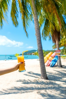 First-person view. girl holds a glass cup of cold mango fresh on the background of a sandy tropical beach. white sand and palm trees. fairytale vacation