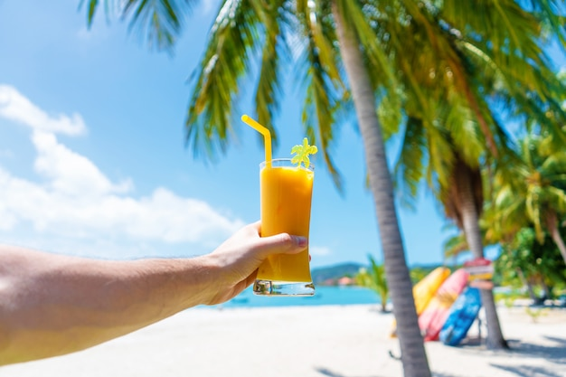 First-person view. girl holds a glass cup of cold mango fresh on the wall of a sandy tropical beach. white sand and palm trees. fairytale vacation