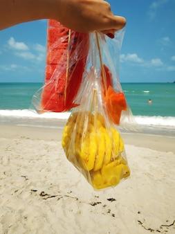 열대 해변에서 휴식을 취하고 과일을 먹는 소녀의 1인칭 시점