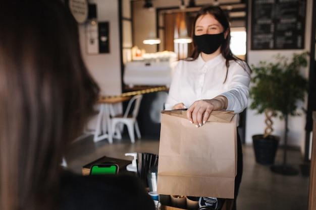 Вид от первого лица клиента берет пакет с кофе и едой от кассира в маске в кафе