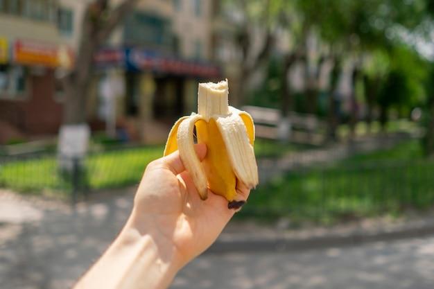 Вид от первого лица руки, держащей свежий спелый банан, еду или закуску на улицах города