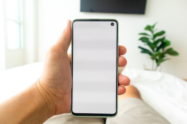 ベッドに横になっているときにスマートフォンを使用して男の一人称のビュー。